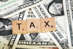 Photo of the word tax on top of money for an article about tax breaks for homeowners.