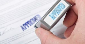 Photo of an approval stamp on a mortgage application for an article about buying after a short sale.