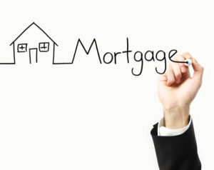 Hand writing out the word mortgage to illustrate points about 15 year mortgages.