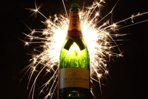 Photo of a bottle of champagne and a firework for an article about New Years Eve 2016.