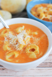 Bowl of creamy tortellini soup for a post about a soup recipe.