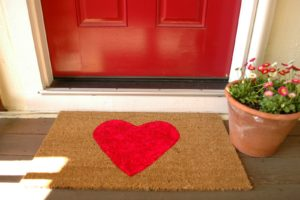 Photo of a red front door with a matching doormat for an article about improving curb appeal.