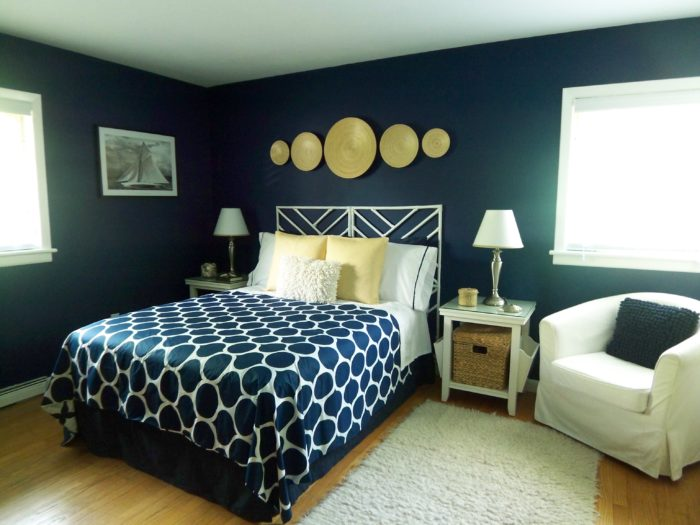 Modern navy blue bedroom as an example of spring home decor trends.