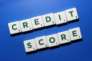"Photo of the words ""credit score"" being spelled out with scrabble tiles for an article about boosting your credit score."