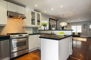 Photo of an updated kitchen with stone countertops for an article about home maintenance mistakes.