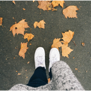Photo of a person walking on fall leaves for an article discussing the question why is autumn a good time to buy?