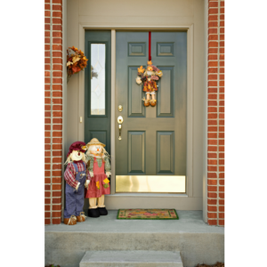 Photo of a green front door with fall decor.